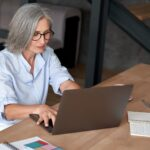 Older mature middle aged woman using laptop computer sitting at work desk.